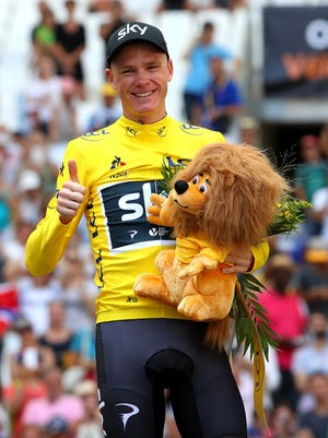 Chris Froome of Great Britain and Team Sky celebrates in the yellow jersey following stage 20 of the Tour de France.
