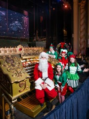 "Santa-clad artistic director Alex Gartner and elves Jack Anderson, 13, (clockwise from top), Savannah Browning, 12, Shayna Bagley, 13, and Ellie Caldwell, 11, pose around the newly refurbished vintage Robert Morton organ at the Saenger Theatre during the Pensacola Children's Chorus rehearsal on Wednesday, December 6, 2017.  The organ, that was installed as part of the Saenger's construction, will play a part in this year's ""Christmas on the Coast"" performance."