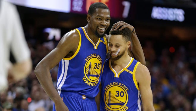 Golden State Warriors' Kevin Durant hugs teammate Stephen Curry.