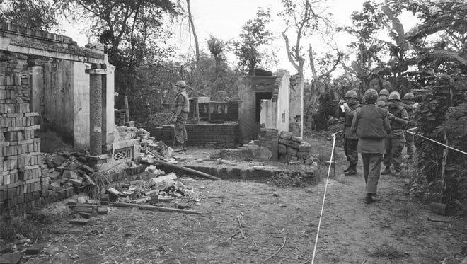 American soldiers look over the remains of a home in My Lai, South Vietnam, in this Jan. 8, 1970 photo. The GIs are in a safe area marked off with white tape, having been swept for booby-traps that have already wounded five soldiers since the investigation of the killing of unarmed civilians by members of the U.S. Army; what would come to be called The My Lai Massacre, began.
