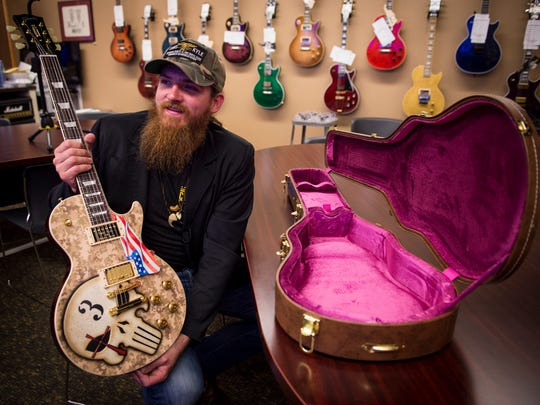 Nashville country artist Tim Montana holds a Gibson Les Paul custom made to benefit the Chris Kyle Foundation at the Gibson Custom Shop, Wednesday, May 11, 2016, in Nashville, Tenn.