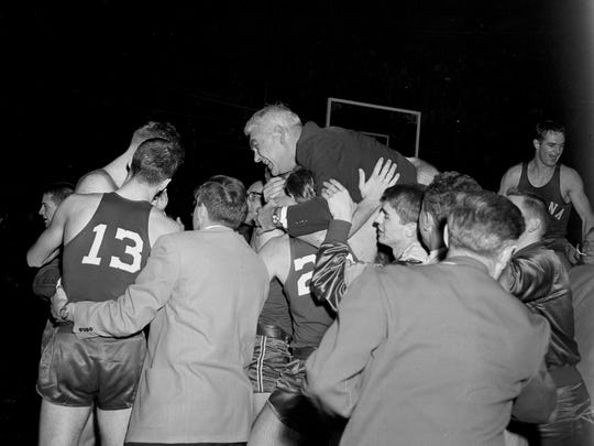 Indiana coach Branch McCracken is carried off the floor by the Hoosiers after they defeated Kansas in the NCAA finals in Kansas City, Missouri, March 18, 1953. (AP Photo)