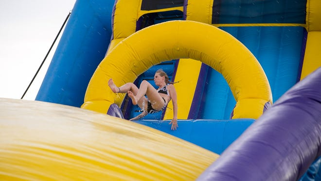 Lorena Palmer goes down a water slide at Slide Across America at Salt River Fields at Talking Stick on Friday, August 7, 2015.