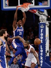 Philadelphia 76ers' Joel Embiid (21) dunks in front of New York Knicks' Kyle O'Quinn (9) during the second half of an NBA basketball game Thursday, March 15, 2018, in New York.
