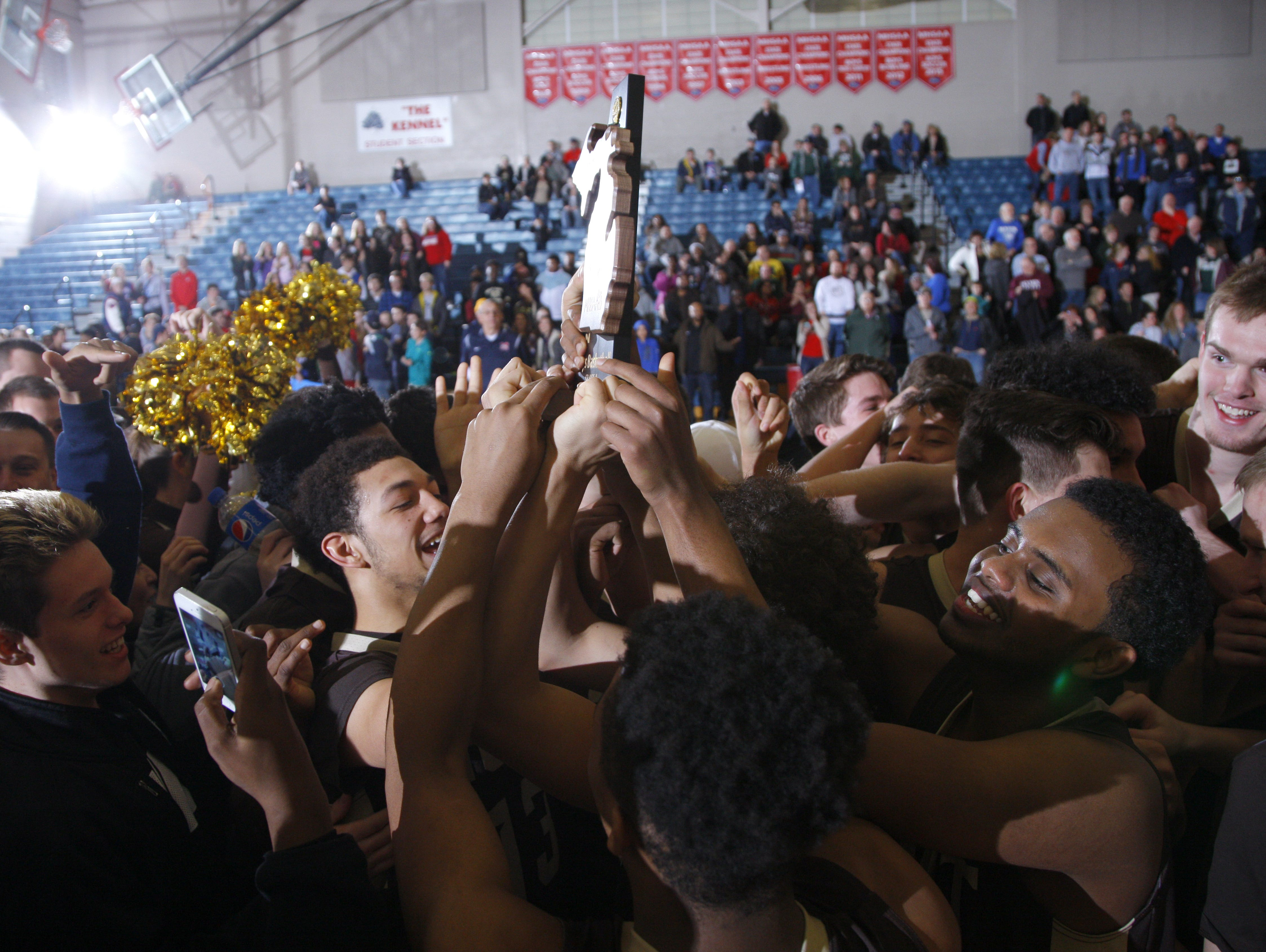 Holt players raise their district championship trophy after defeating Mason 74-44, Friday, March 10, 2017, in Mason, Mich.