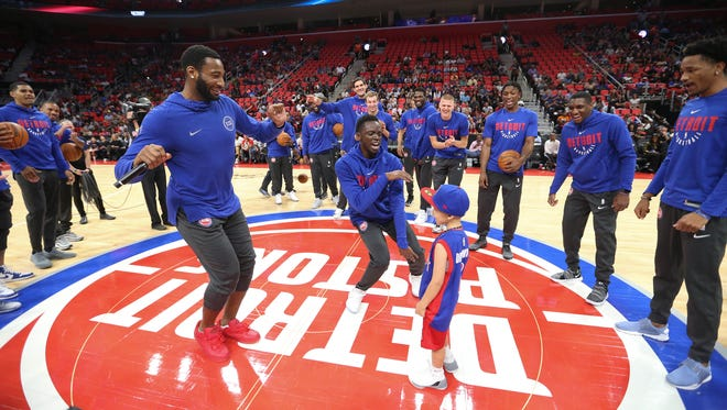 The Detroit Pistons Andre Drummond and Reggie Jackson dance with Zack Jaafar from Dearborn Heights during meet the team day at Little Caesars Arena in Detroit  Tuesday, October 3, 2017.
