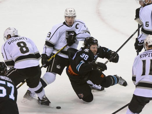 Los Angeles Kings right wing Dustin Brown (23) checks San Jose Sharks center Logan Couture (39) during the second period in game seven.