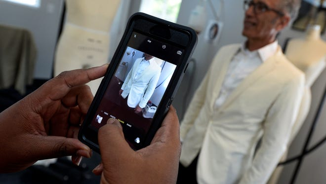 Fashion design student Kristopher Kelley takes a photograph of a muslin mock-up seersucker sport jacket worn by O'More College of Design President David Rosen on Tuesday, Aug. 9, 2016, in Franklin.