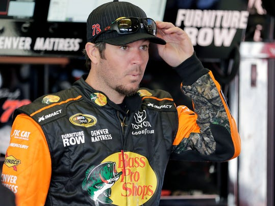 Martin Truex Jr. takes a break in his garage during a practice session for the NASCAR Daytona 500 auto race at Daytona International Speedway, Saturday, Feb. 13, 2016, in Daytona Beach, Fla. (AP Photo/Terry Renna)