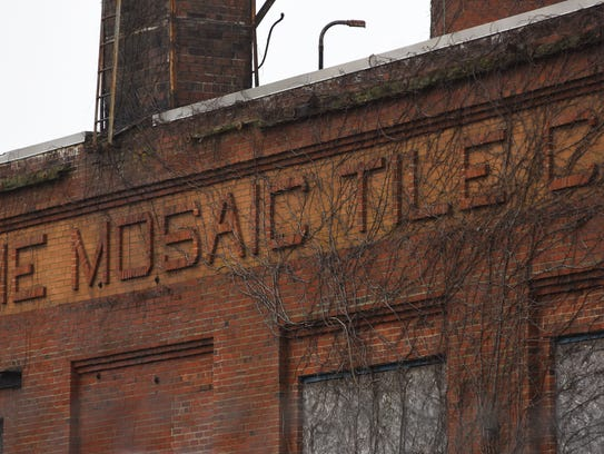 Ivy clings to the brick sign proclaiming the abandoned