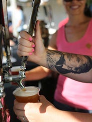 Kelsey Fretwell pours a pint of Gilgamesh's DJ Jazzy Hef as Riverfront Park fills with revelers for Bite and Brew of Salem, now known as Cherryfest NW.