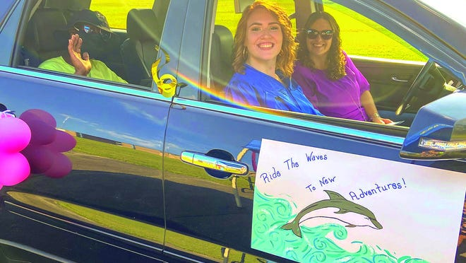 Chelsea G. Dietz, center, waits in a vehicle with her family and friends for her turn to walk on the red carpet at Pamlico Community College's drive-thru Commencement ceremony on Friday, July 31.
