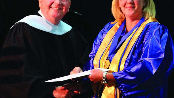 Pamlico Community College President Jim Ross, left, presents Noelle Baker with her associate's degree in Electroneurodiagnostic Technology (EDT) during the 2019 Commencement ceremony. PCC's EDT program can be completed entirely online.
