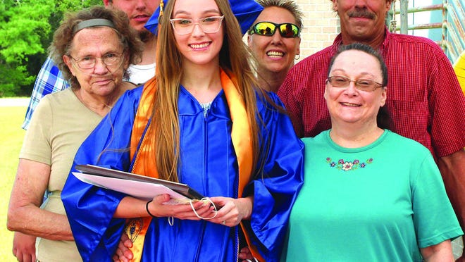 Samantha Dawn Armstrong-Plumley, in cap and gown, is joined by her parents and other family members at Pamlico Community College's July 31 Commencement ceremony. Not pictured is her husband, Michael Plumley, who is a U.S. Marine.
