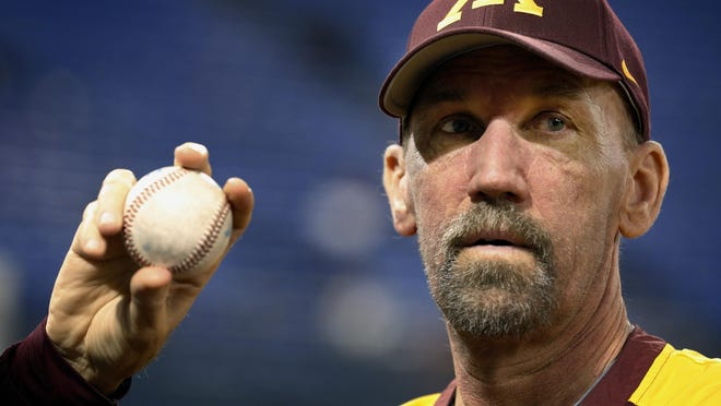Minnesota Gophers pitching coach Todd Oakes holds a ball before an NCAA baseball game on Feb. 27, 2013, in Minneapolis. Oakes died after a battle with leukemia.