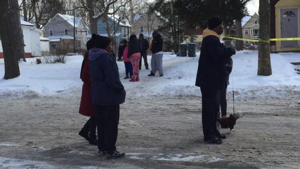 Neighbors gather at the crime scene on Magnolia Street.