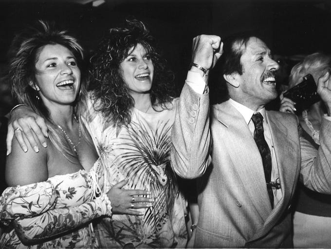 Sonny Bono cheers the election results of Palm Springs mayoral race with daughter Christy Bono-Fasce (left) and wife Mary Bono at their celebration headquarters at Maxims de Paris Suite Hotel in Palm Springs on April 13, 1988.