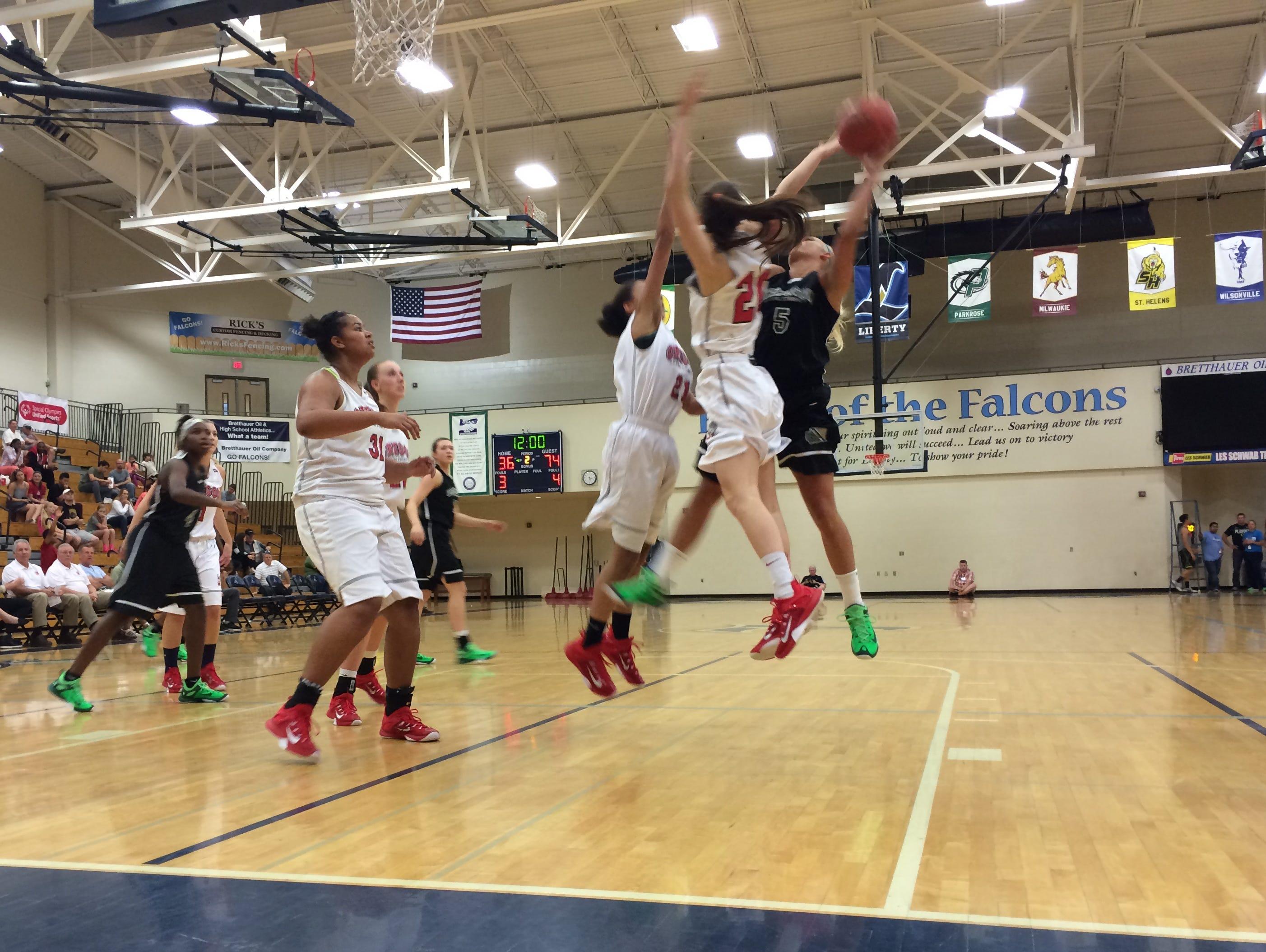 Washington's Madison Hovren's shot is contested by Oregon's Nohea Waiwaiole.