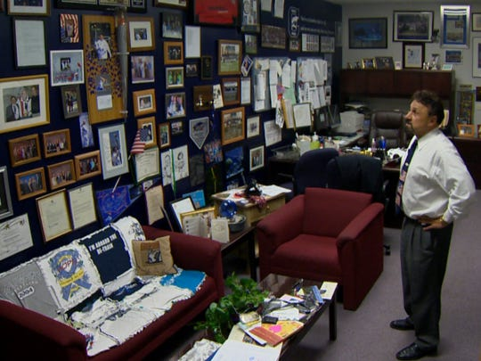 Frank DeAngelis, principal of Columbine High School in Colorado, looks at what he calls his Wall of '99 in his office at the school. He has worked to rebuild his school community and been called on to help others across the country do the same.