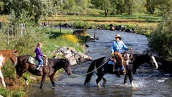 Kim Johnson, of the X-Diamond Ranch, leads Emily Wasylenko, 8, of Phoenix, over the South Fork of the Little Colorado River during a horsback ride September 14, 2006.