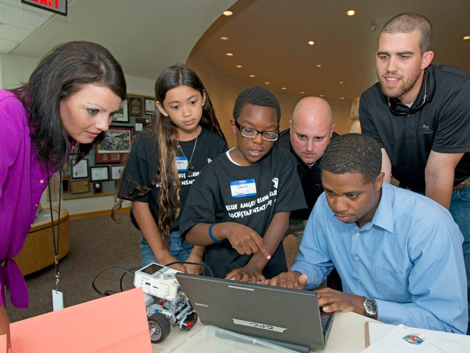 Gulf Power employees Kay Hill, left, Frank Browne, center, A.J McCorvey, right seated, and Jimmy Haney, right standing, receives help in programing their robot for competition from Blue Angels Elementary School students Maegan Kramer, left center, and Javin Augustine, center.