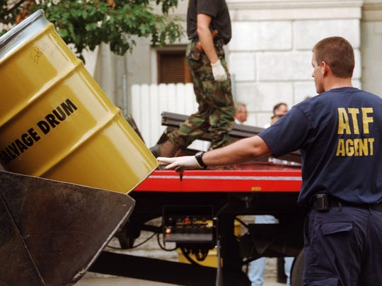 An ATF agent directs a barrel marked exhibits Monday morning after the truck that rammed into the Tippecanoe County Courthouse Sunday night. (3 aug. 98)