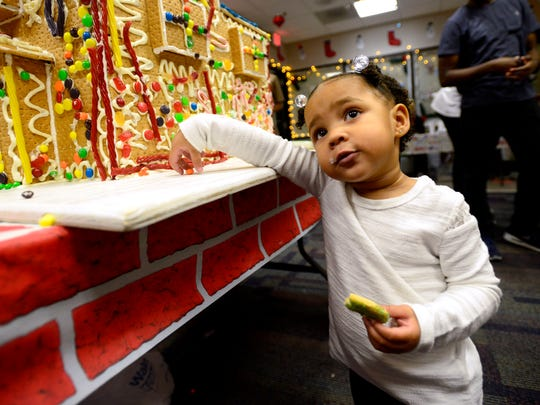 Kennedy DeLaney, 20-months-old, helps decorate a gingerbread