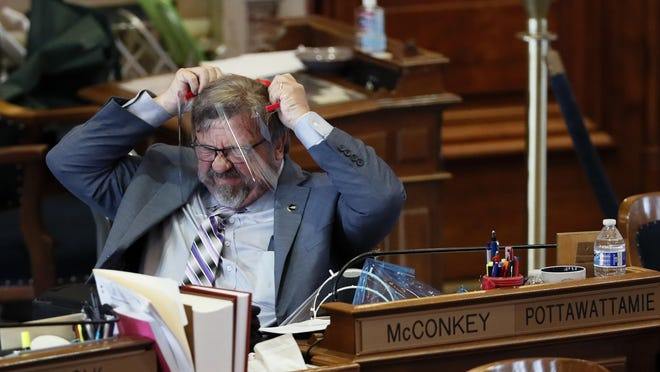 State Rep. Charlie McConkey, D-Council Bluffs, adjusts his face guard in the Iowa House chambers Wednesday at the Statehouse in Des Moines. Lawmakers returned Wednesday after suspending the session when the coronavirus pandemic surfaced in Iowa in March, prompting state officials to close the state Capitol.
