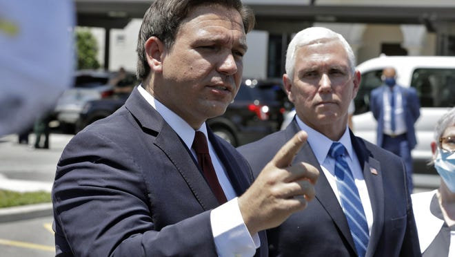Florida Gov. Ron DeSantis, left, gestures as he speaks to the media with Vice President Mike Pence delivering personal protective equipment to the Westminster Baldwin Park Wednesday, May 20, 2020, in Orlando, Fla., as part of the initiative to deliver PPE to more than 15,000 nursing homes across America.   Pence is also scheduled to participate in a roundtable discussion with hospitality and tourism industry leaders to discuss their plans for re-opening during the coronavirus outbreak.