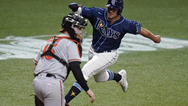 Tampa Bay Rays' Hunter Renfroe scores around Baltimore Orioles catcher Chance Sisco on a sacrifice fly by Ji-Man Choi during the sixth inning of Tuesday's game in St. Petersburg, Fla.