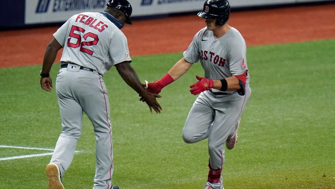 Boston Red Sox's Bobby Dalbec celebrates with third base coach Carlos Febles (52) after his solo home run off Tampa Bay Rays pitcher Josh Fleming during the fifth inning of a baseball game Thursday, Sept. 10, 2020, in St. Petersburg, Fla.