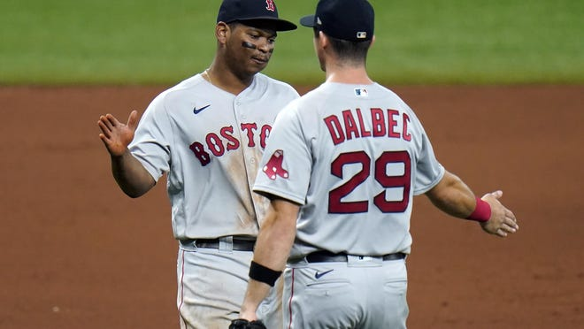 Boston Red Sox third baseman Rafael Devers, left, and first baseman Bobby Dalbec celebrate after the team defeated the Tampa Bay Rays during a baseball game Thursday, Sept. 10, 2020, in St. Petersburg, Fla.