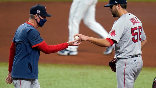Red Sox pitcher Matt Hall hands the ball to manager Ron Roenicke as he is taken out of Friday night's game against the Rays in the fourth inning.