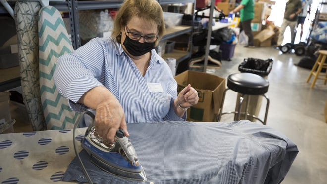 Linda Guilbert irons newly donated clothes at the Ladies of Charity thrift store.