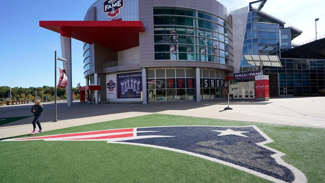 A passer-by walks past a New England Patriots football team logo near the Patriots ProShop at Gillette Stadium, Sunday, Oct. 11, 2020, in Foxborough, Mass. The NFL has postponed the Denver Broncos-New England Patriots game due to another positive coronavirus test with the Patriots.