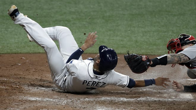 Tampa Bay Rays' Michael Perez, left, scores ahead of the tag by Boston Red Sox catcher Christian Vazquez on an RBI triple by Austin Meadows during the fifth inning Tuesday night in St. Petersburg, Fla.