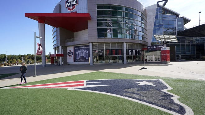 A passer-by walks past a New England Patriots football team logo near the Patriots ProShop at Gillette Stadium on Sunday in Foxborough. The NFL has postponed the Denver Broncos-New England Patriots game due to another positive coronavirus test with the Patriots.