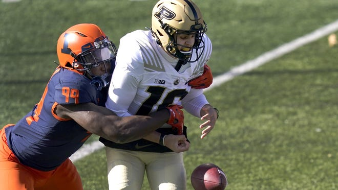 Illinois defensive lineman Owen Carney Jr., left, strips Purdue quarterback Aidan O'Connell of the ball during the first half of Saturday's game, in Champaign.
