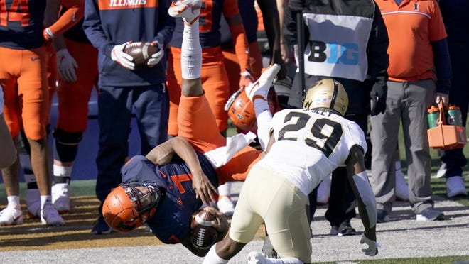 Illinois quarterback Coran Taylor (7) is upended by Purdue cornerback Simeon Smiley during the first half Saturday, Oct. 31 in Champaign.