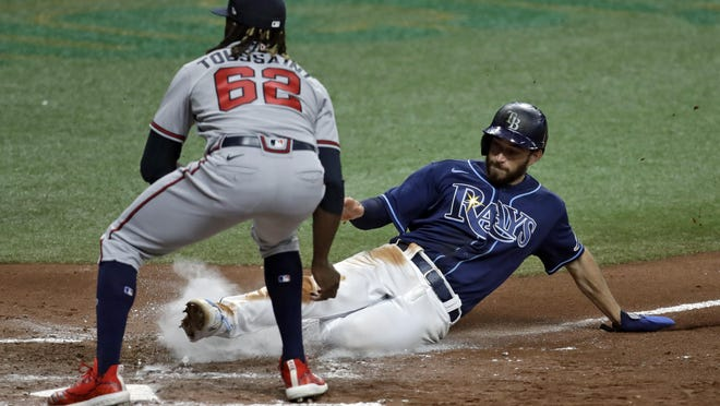 Tampa Bay Rays' Brandon Lowe scores on a wild pitch by Atlanta Braves relief pitcher Touki Toussaint during the fourth inning of a baseball game Monday, July 27, 2020, in St. Petersburg, Fla.