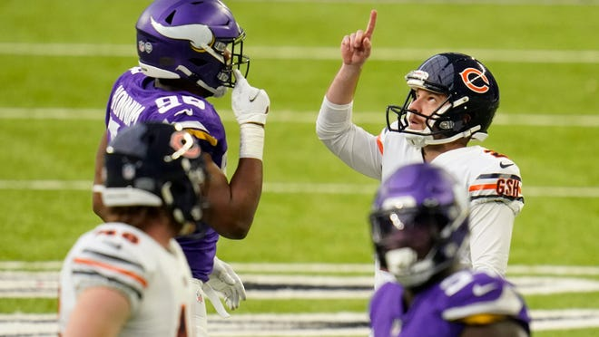 Chicago Bears place kicker Cairo Santos celebrates in front of Minnesota Vikings defensive end D.J. Wonnum, left, after kicking a 48-yard field goal during the second half of an NFL football game, Sunday, Dec. 20, 2020, in Minneapolis. (AP Photo/Jim Mone)