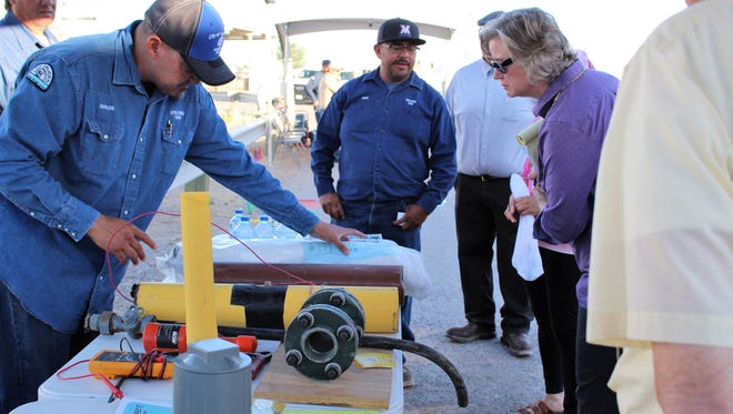 Carlos Lopez, gas cathodic protection technician, explains to a member of the Neighborhood Leadership Academy how providing natural gas to residences, businesses and different types of commercial accounts requires a variety of sizes and types of gas piping.