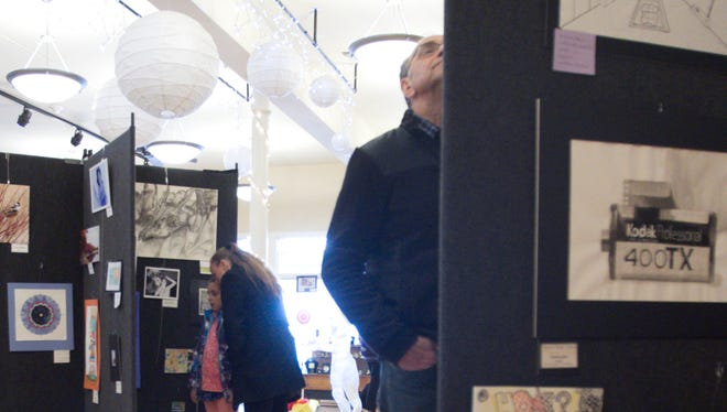 John Vlahos, of Howell, center, looks at student artwork Saturday on display at the Livingston Arts Council's Got ART student exhibition. The exhibition is open through March 29 at The Opera House in downtown Howell.