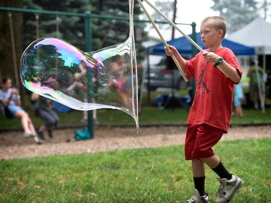 "A child blows a ""super bubble,"" one of many children's activities available at the Spinstock festival, which moves to Coleman Memorial Park for the first time on Saturday, June 15."