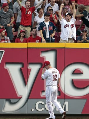 Cincinnati Reds right fielder Jay Bruce (32) reacts as a Indians fan cheers after catching a two-run home run off the bat of Cleveland Indians right fielder Brandon Moss (44) during the top of the third inning of the MLB game between the Cincinnati Reds and the Cleveland Indians.