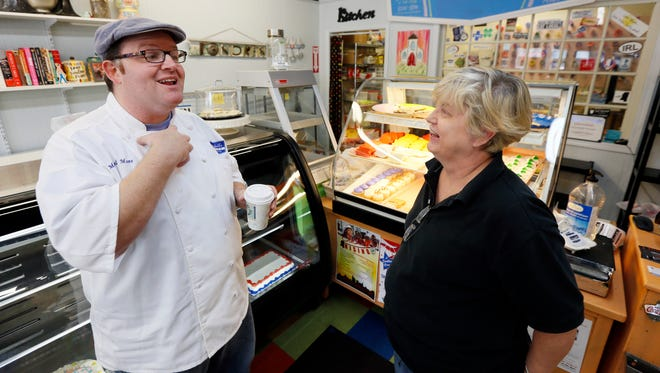 Baker Mitchell Moore, left, talks April 22, 2014, with Tina Fortenberry in his Jackson, Miss., store. He is one of more than 300 businesses in Mississippi and almost 100 more elsewhere who are supporting anti-gay bias by displaying stickers at their establishments.