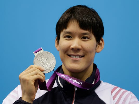FILE- In this Monday, July 30, 2012 file photo, South Korea's Park Tae-hwan poses with his silver medal for the men's 200-meter freestyle swimming final at the Aquatics Centre in the Olympic Park during the 2012 Summer Olympics in London. South Korea's Olympic committee lifted its ban on Park Tae-hwan on Friday, allowing the former Olympic swimming champion to compete in the Rio de Janeiro Games. (AP Photo/Michael Sohn, File)