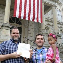 Andrew Kohn (left) and Donald Jones (right) holding their children.