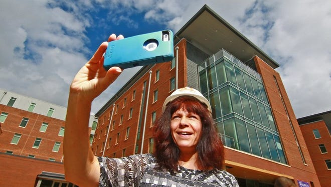 Jackie Todd, Clemson University director of internal communications, takes a photograph on the steps of the Core Campus Project dormitories.