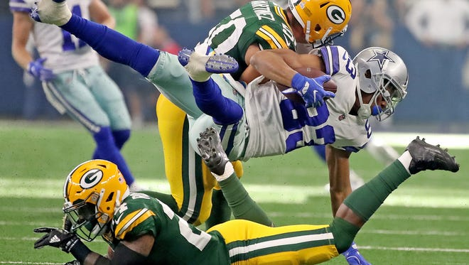 Green Bay Packers inside linebacker Blake Martinez (top) and cornerback Quinten Rollins (bottom) upend wide receiver Terrance Williams (83) of the Dallas Cowboys on Sunday, Oct. 8, 2017 at AT&T Stadium in Arlington, Texas.